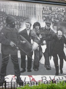 This mural depicts the banner on the ground over the body of one of the boys while another wounded is carried off for treatment with the priest waving the white flag of surrender - he was shot too.